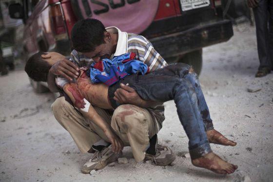 Un hombre sirio llora sobre el cuerpo de su hijo cerca del hospital de Aleppo en Siria. Octubre de 2012, fotografía ganadora del premio Pulitzer, de Manu Brabo